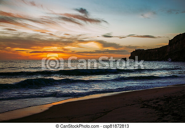 Nazare, Portugal: Sunset over Atlantic Ocean seen from the beach - csp81872813