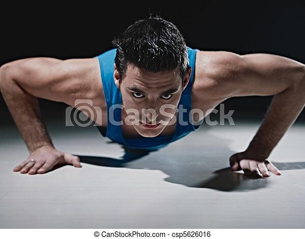 Un hombre haciendo flexiones de fondo negro - csp5626016