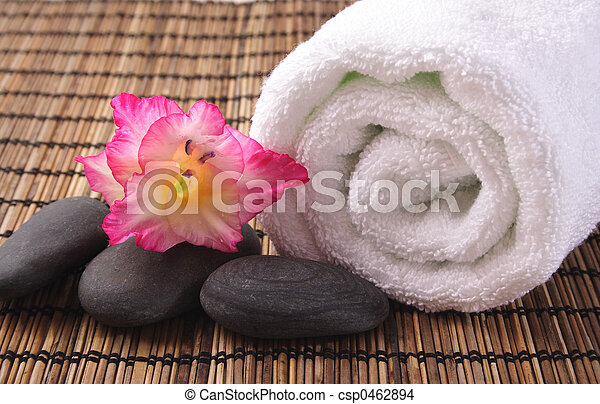 Gladiola, guijarros negros y toalla blanca en el tapete de bambú - csp0462894