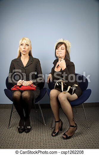 Nervous businesswoman seated next to a bold woman - csp1262208