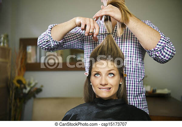 nervous woman in hairdresser shop cutting long hair - csp15173707