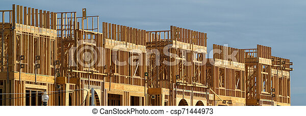 New apartment building under construction on sunny day on blue sky background - csp71444973