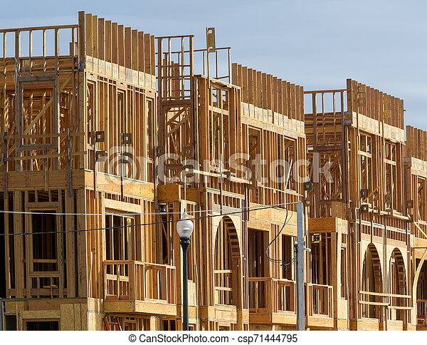 New apartment building under construction on sunny day on blue sky background - csp71444795