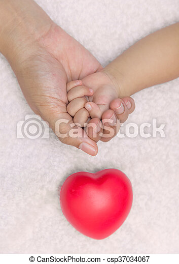 New born baby hand in mom palm with red heart - csp37034067