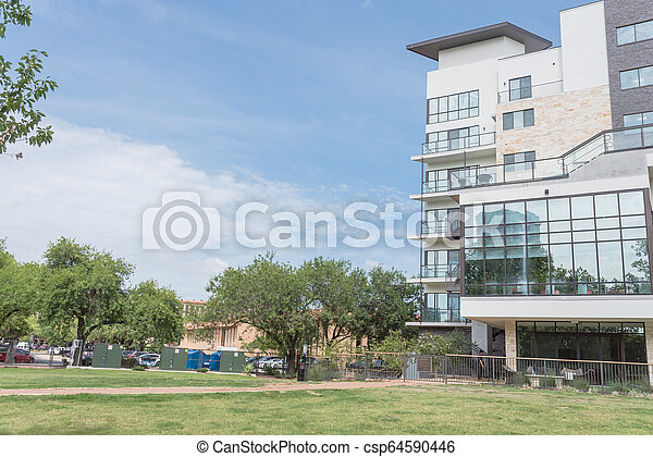 New development apartment building with large grass lawn - csp64590446