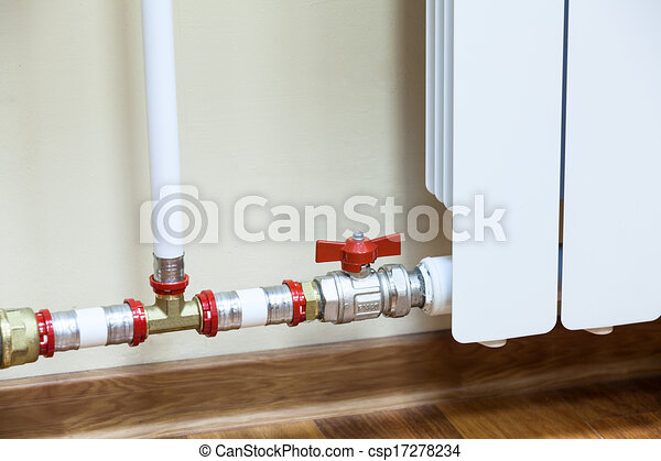 New installed central heating radiator with valve on pipe.
