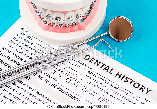 New patient medical form with model tooth and dental instruments. - csp77380195