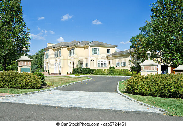 New single family home with gate posts and long driveway in suburban Philadelphia, Pennsylvania.  French Provincial style. - csp5724451