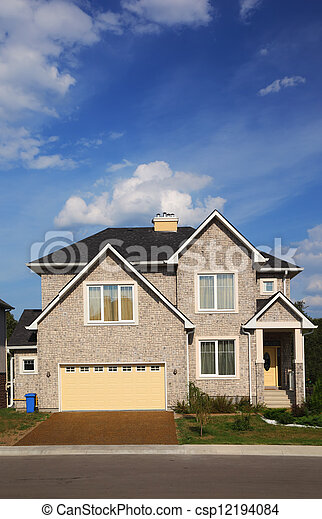 New two-storied beige stone cottage with yellow garage and brown roof. - csp12194084