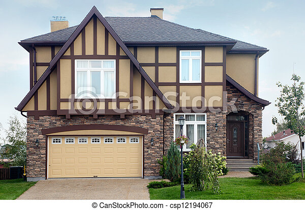 New two-storied brown stone cottage with beige garage and roof. - csp12194067