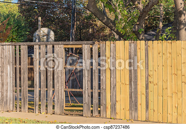 New wooden fence near collapsed slats in backyard of residential house with mature trees in suburban Dallas, Texas - csp87237486