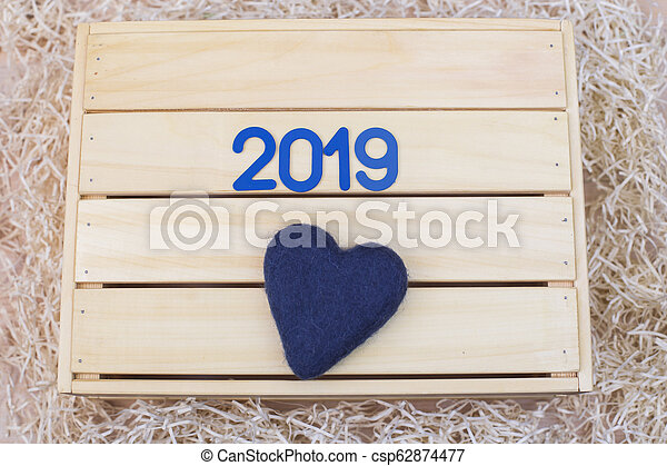 New Year 2019. Symbol with and a heart on a wooden background - csp62874477