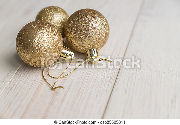 New year and Christmas background - three golden balls on wooden background. - csp85625811