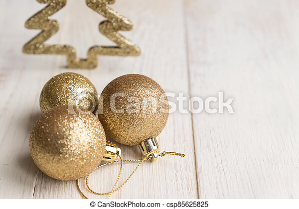New year and Christmas background - three golden balls on wooden background. - csp85625825