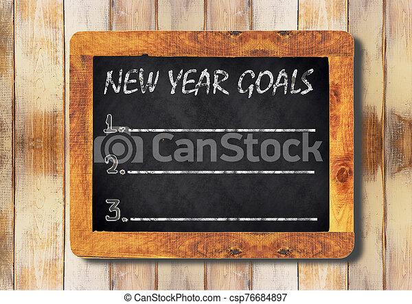 new year goals chalk on the blackboard - csp76684897