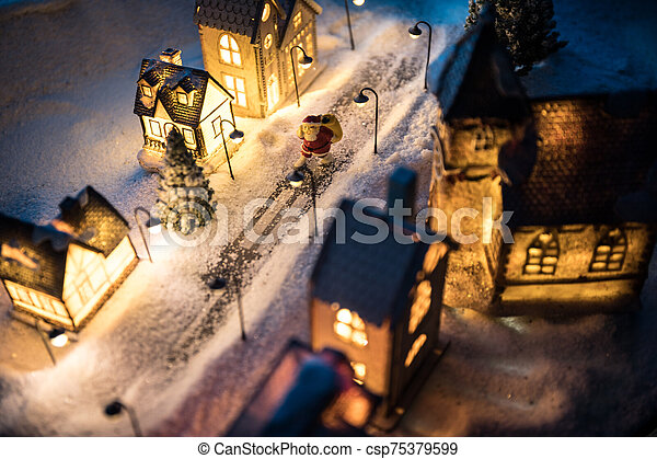 New Year miniature house in the snow at night with fir tree. - csp75379599