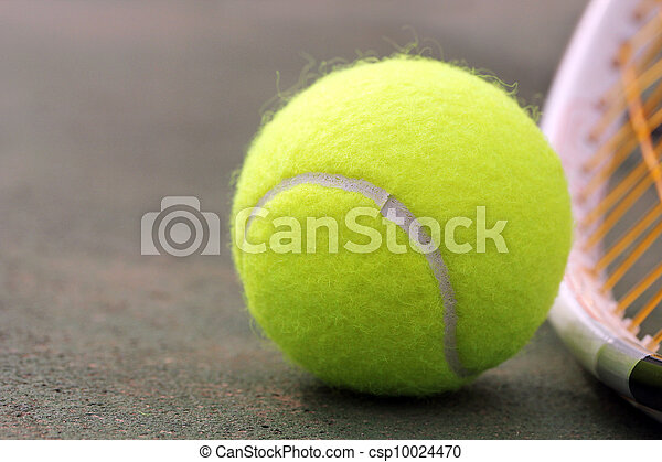 New yellow colored tennis ball placed next to racket(racquet) on synthetic(hard) tennis court surface with copy space for text on the left - csp10024470