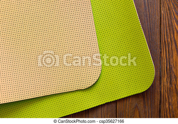 07ca7b99b05ae New yoga mat is light green and beige on a wooden background. facilities  for training and yoga. diagonal. the concept of love to a healthy lifestyle.  weight ...