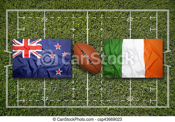 New Zealand vs. Ireland flags on green rugby field
