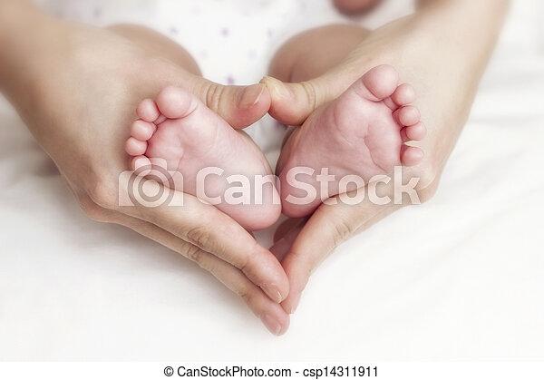 Newborn baby feet in the mother hands - csp14311911