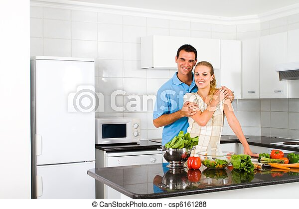 newlywed couple in home kitchen - csp6161288