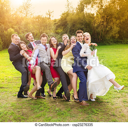 Newlyweds with guest posing in park - csp23276335