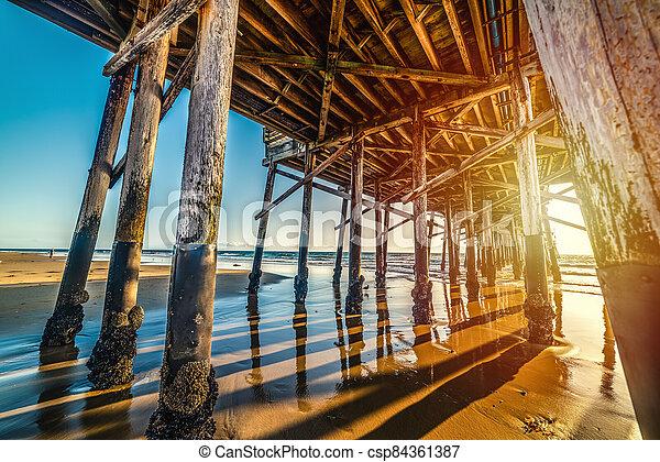 Newport Beach wooden pier seen from the ground at sunset - csp84361387