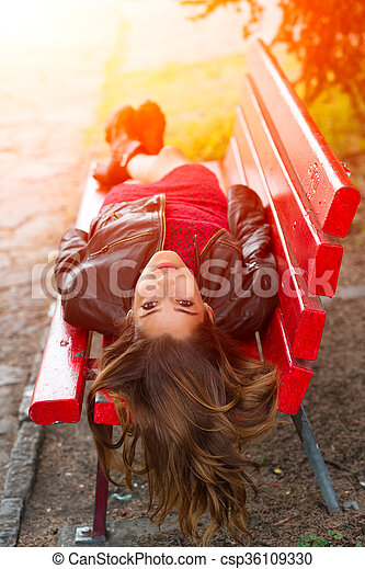 ng girl lying on a red bench with long hair back - csp36109330