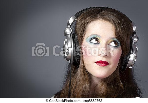 Hermosa chica con auriculares en un fondo gris oscuro - csp8882763