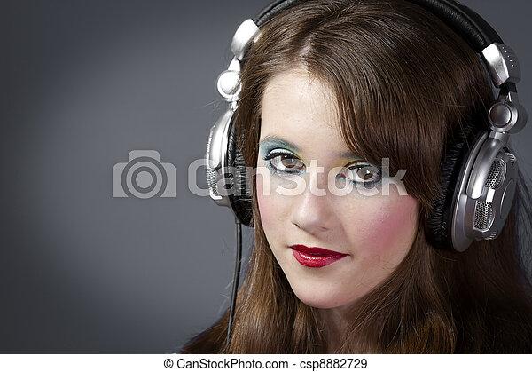 Una chica con auriculares en un fondo gris oscuro - csp8882729