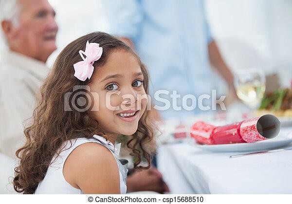 Una niña sentada en la mesa para la cena de Navidad - csp15688510