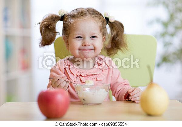 Niña comiendo con cuchara - csp69355554