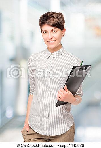 Una joven contable con una carpeta en la oficina - csp51445826