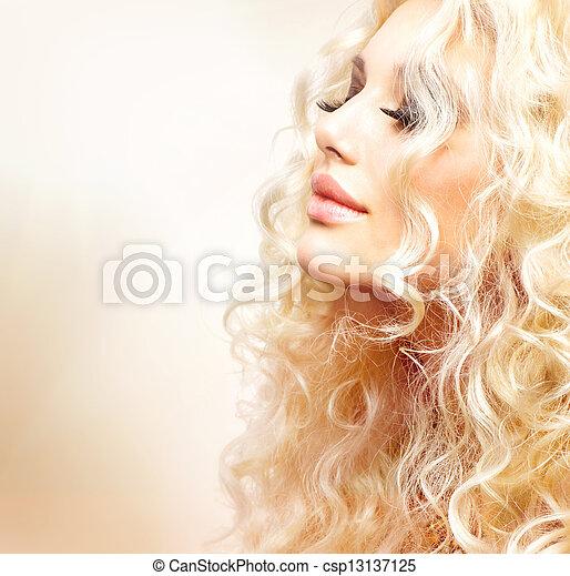 Una chica hermosa con cabello rubio rizado - csp13137125