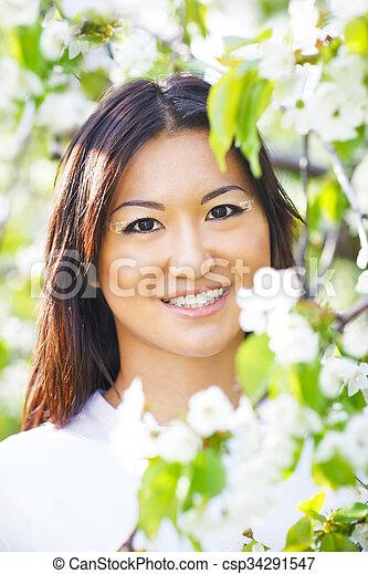 Una joven feliz sonriente en el jardín de primavera - csp34291547