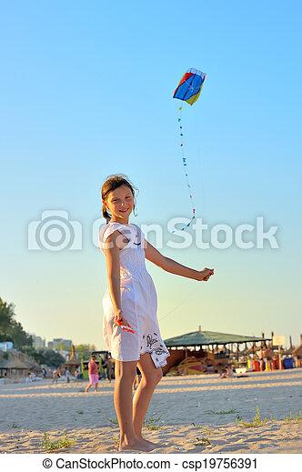 Una joven volando una cometa en la playa - csp19756391