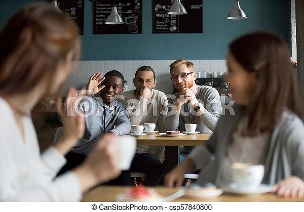 Un hombre sonriente africano saludando a las chicas en el café - csp57840800