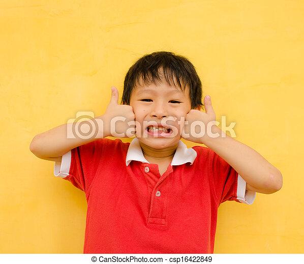 Un chico feliz sonríe y muestra pulgares arriba - csp16422849