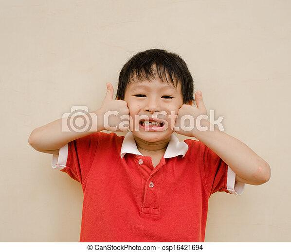 Un chico feliz sonríe y muestra pulgares arriba - csp16421694