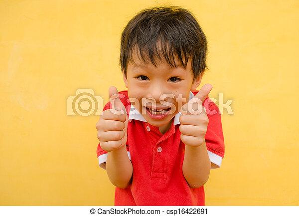 Un chico feliz sonríe y muestra pulgares arriba - csp16422691