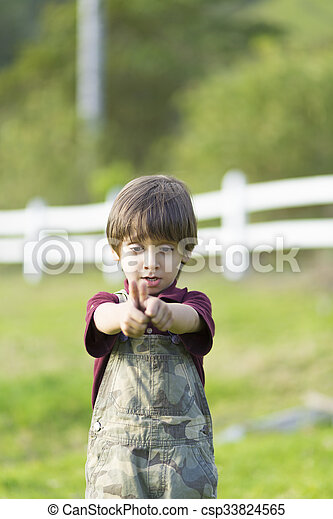 Un chico encantador y feliz mostrando los pulgares - csp33824565