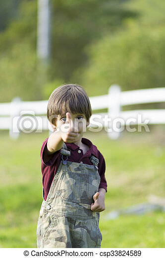 Un chico encantador y feliz mostrando los pulgares - csp33824589