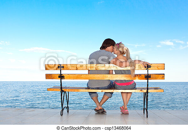 Un novio romántico y una chica besándose en un banco en la playa - csp13468064