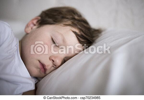 Un niño de 3 años durmiendo en la cama - csp70234985