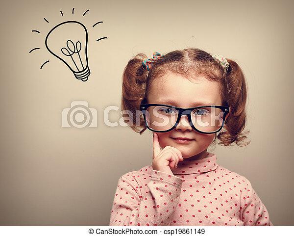 Pensando en un chico feliz con gafas con una bombilla sobre la cabeza - csp19861149