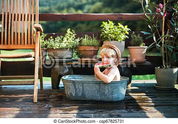 Un niño pequeño con un sombrero en el baño al aire libre en el jardín en verano, comiendo sandía. - csp67825731