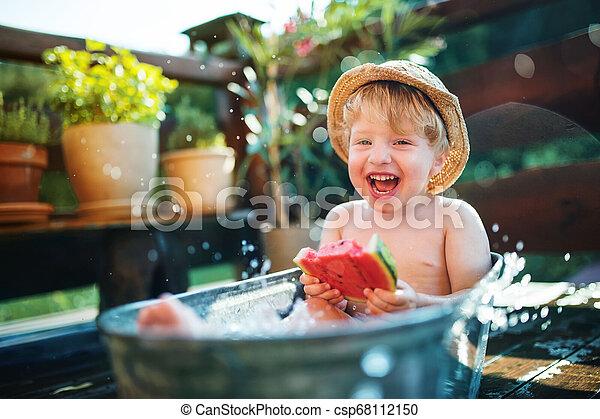 Un niño pequeño con un sombrero en el baño al aire libre en el jardín en verano, comiendo sandía. - csp68112150