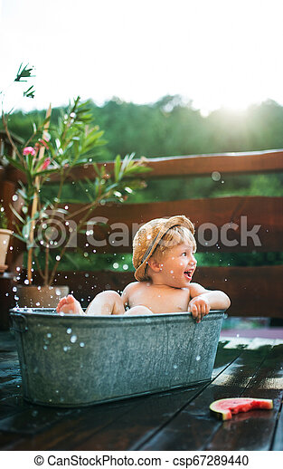 Un niño pequeño con un sombrero en el baño al aire libre en el jardín en verano, comiendo sandía. - csp67289440