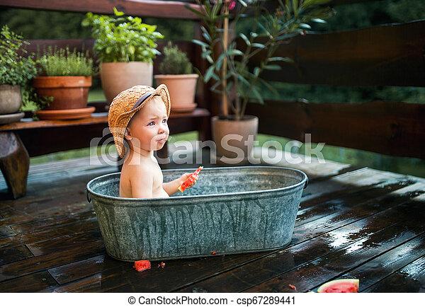 Un niño pequeño con un sombrero en el baño al aire libre en el jardín en verano, comiendo sandía. - csp67289441