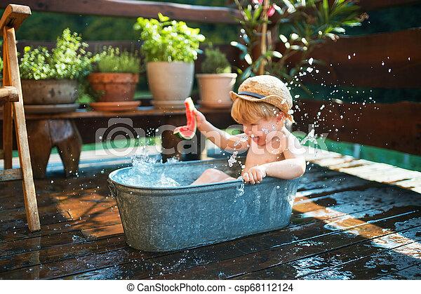 Un niño pequeño con un sombrero en el baño al aire libre en el jardín en verano, comiendo sandía. - csp68112124